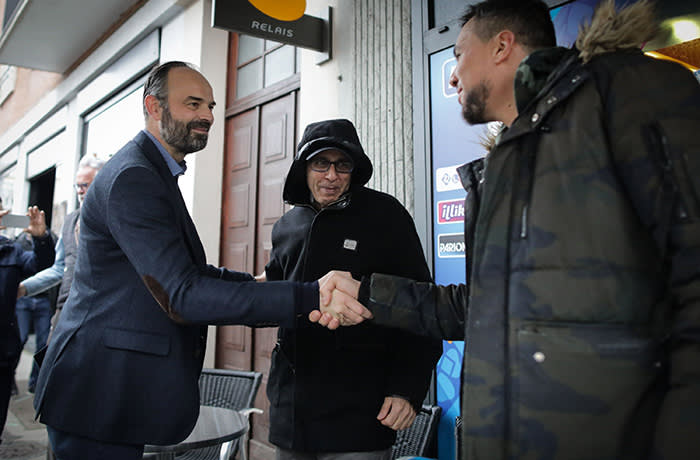 Prime Minister and candidate in Le Havre's mayoral elections Edouard Philippe (C) shakes hands with people in a street of Le Havre, northwestern France, on February 1, 2020 as part of his electoral campaign. - Mayoral elections take place in March 2020. (Photo by LOU BENOIST / AFP) (Photo by LOU BENOIST/AFP via Getty Images)