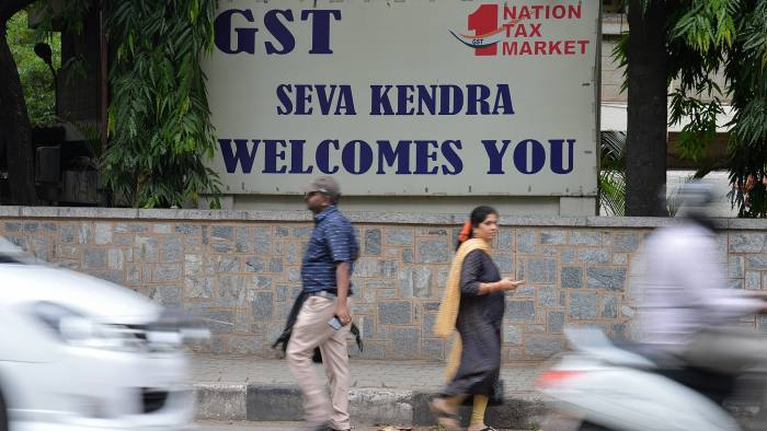 Pedestrians walk in front of a board advertising Goods and Service Tax (GST) in front of the Central Goods and Service Tax office in Bangalore on June 28, 2018. / AFP PHOTO / MANJUNATH KIRAN