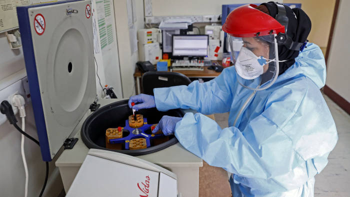 In this Sunday, March 1, 2020 photo, a paramedic works with a centrifuge to test blood samples taken from patients suspected of being infected with the new coronavirus, at a hospital in Tehran, Iran. A member of a council that advises Iran's supreme leader died Monday after falling sick from the new coronavirus, becoming the first top official to succumb to the illness striking both citizens and leaders of the Islamic Republic. (Ali Shirband/Mizan News Agency via AP)