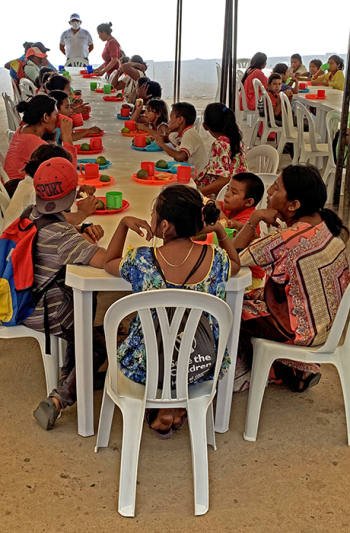 Venezuelan refugees eat a free meal at a soup kitchen set up by the UN World Food Programme in the Colombian border town of Paraguachon. They serve 2,600 breakfasts and lunches per day.