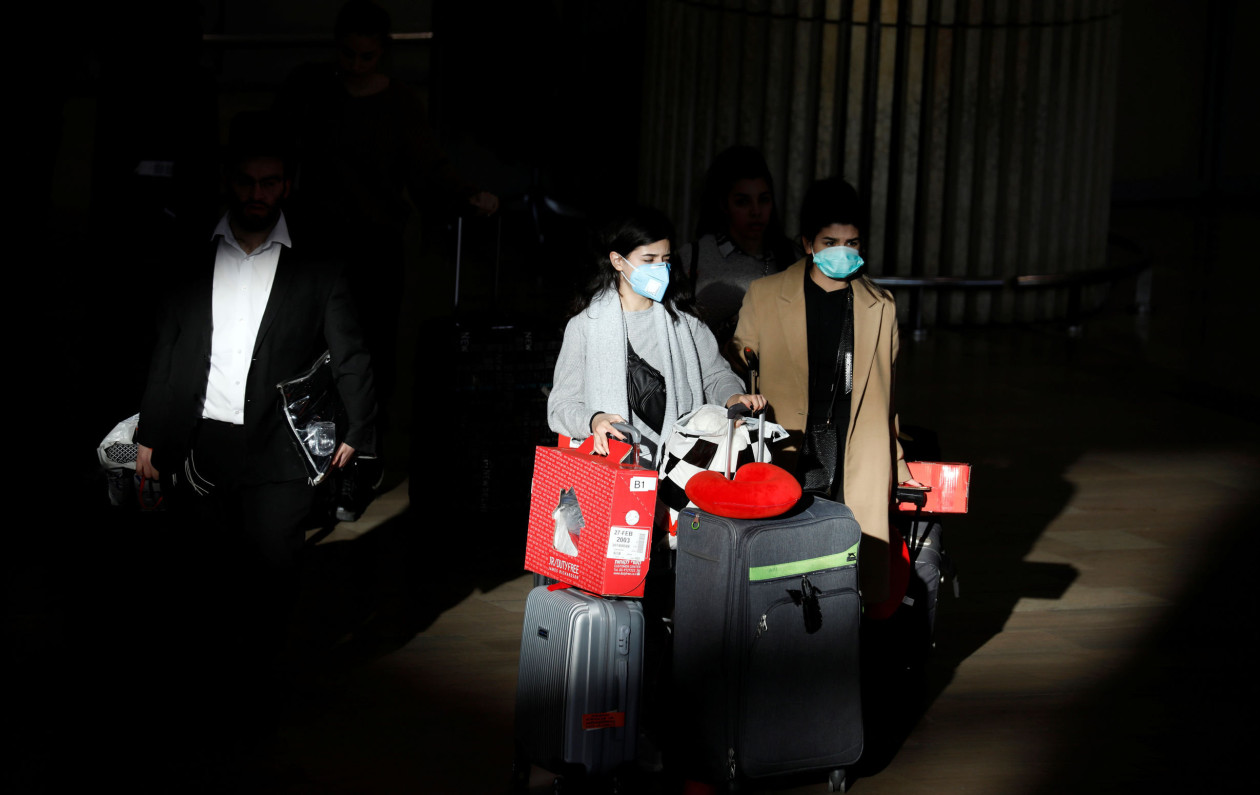 Travellers pull their suitcases while wearing masks in a terminal at Ben Gurion International airport in Lod, near Tel Aviv, Israel February 27, 2020. REUTERS/Amir Cohen