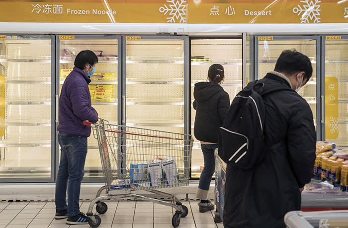 Customers walk past near empty shelves in frozen food refrigerators at a supermarket in Shanghai, China, on Wednesday, Feb. 12, 2020. The Chinese Communist Party's top decision body urged the nation to meet its economic targets this year even amid the downward pressure from the coronavirus shutdowns. Photographer: Qilai Shen/Bloomberg