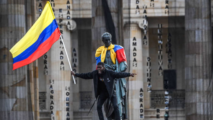 A man waves a national flag atop a statue of Simón Bolívar who led the independence of Colombia and other South American nations