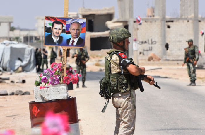 Members of Russian and Syrian forces stand guard near posters of Syrian President Bashar al-Assad and his Russian counterpart Vladimir Putin at the Abu Duhur crossing on the eastern edge of Idlib province on August 20, 2018. - Civilians are coming from rebel-held areas in Idlib province and entering regime-held territories through the Abu Duhur crossing, some of them returning to their villages that were recaptured by the regime forces earlier this year. (Photo by George OURFALIAN / AFP) (Photo credit should read GEORGE OURFALIAN/AFP via Getty Images)