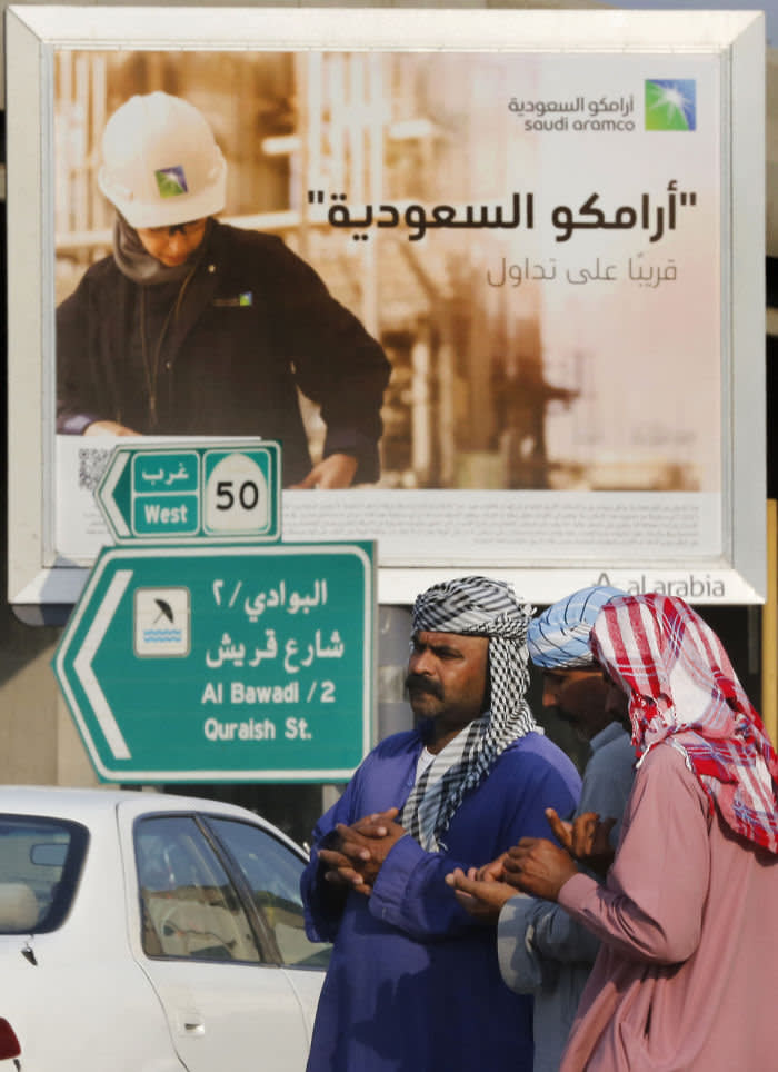Workers are waiting in front of a billboard advertising the state oil giant Saudi Arabia Aramco with Arabic inscriptions: