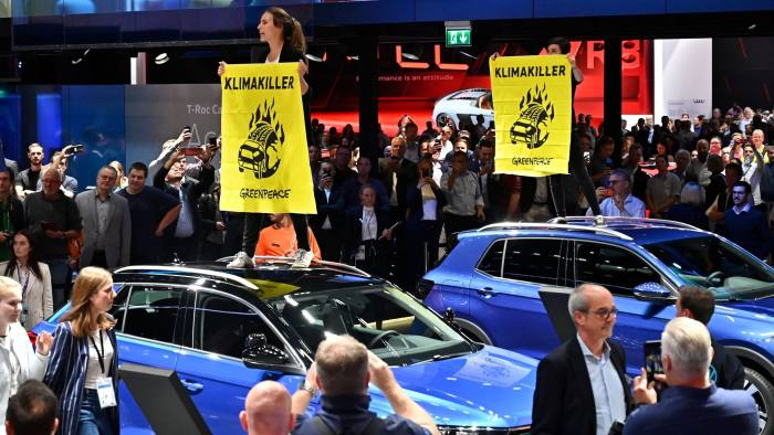 Greenpeace activists standing on Volkswagen (VW) cars hold posters reading