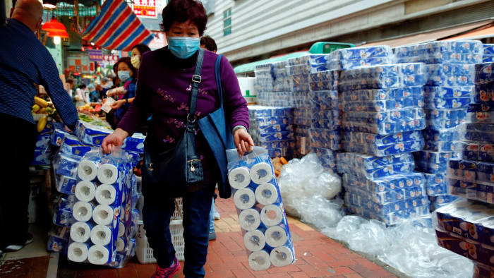 FILE PHOTO: File picture of a customer picking up rolls of toilet paper at a Hong Kong market following the coronavirus outbreak February 8, 2020. REUTERS/Tyrone Siu/File Photo