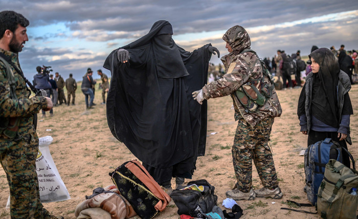 A member of the Kurdish-led Syrian Democratic Forces (SDF) searches a woman after she left the IS group's last holdout of Baghouz, in Syria's northern Deir Ezzor province on February 27, 2019. (Photo by Bulent KILIC / AFP) (Photo by BULENT KILIC/AFP via Getty Images)