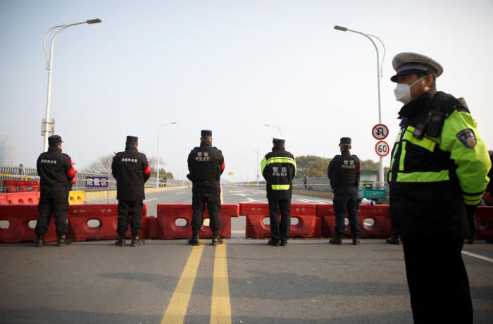 Police stand at a checkpoint at the Jiujiang Yangtze River Bridge that crosses from Hubei province into Jiujiang, Jiangxi province, China, as the country is hit by an outbreak of a new coronavirus, January 31, 2020. Police and security personell lined up in formation at the checkpoint after the local propaganda department granted access to foreign media. REUTERS/Thomas Peter
