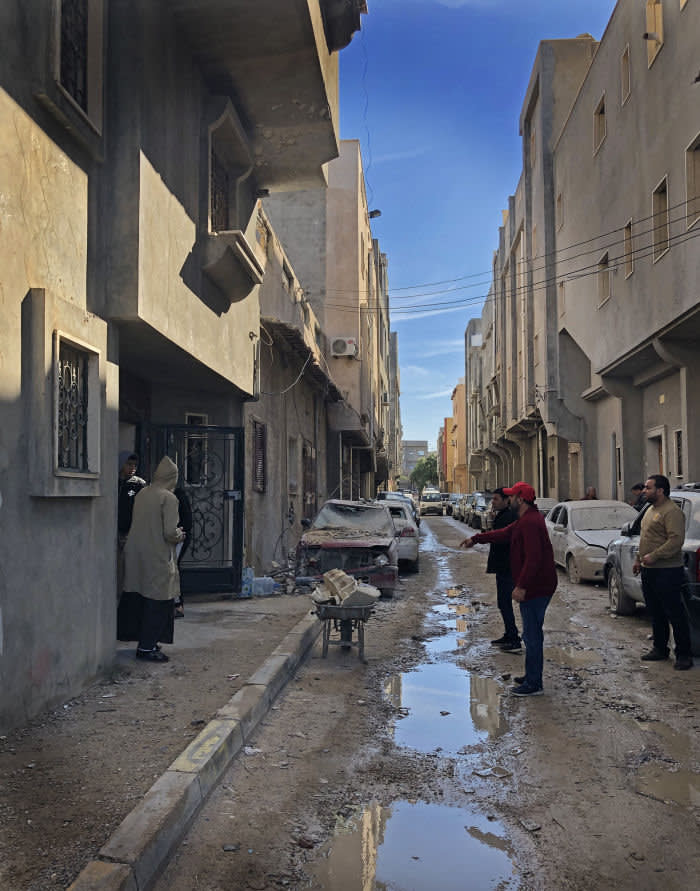 Libya Andrew England Men inspect the damage in their street in a southern neighbourhood of Tripoli, hours after a rocket struck a house.