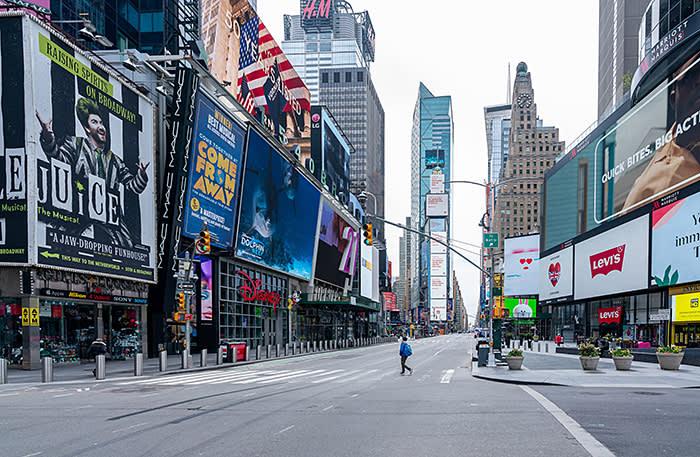 NEW YORK, NY - 20 avril: une personne traverse la rue dans le très calme Times Square le 20 avril 2020 à New York. Lors de son briefing quotidien sur les coronavirus (COVID-19), le gouverneur de New York, Andrew Cuomo, a déclaré que le nombre de morts était tombé en dessous de 500 en 24 heures pour la première fois depuis le début de la pandémie. (Photo de David Dee Delgado / Getty Images)