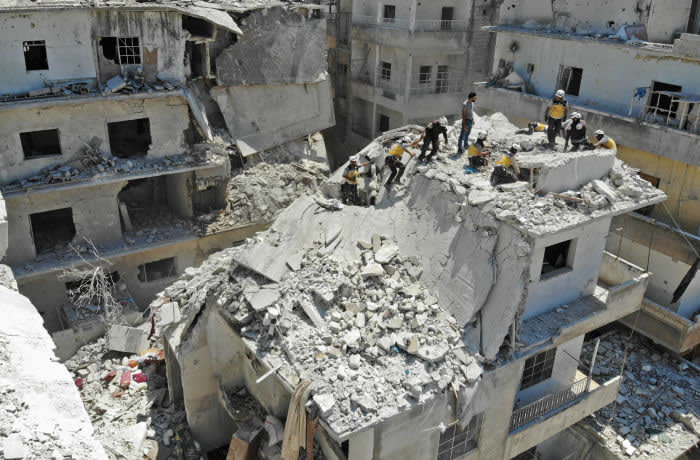 EDITORS NOTE: Graphic content / Members of the Syrian Civil Defence (White Helmets) search for victims at the site of a reported air strike on the town of Ariha, in the south of Syria's Idlib province on July 27, 2019. - Regime airstrikes on July 27 killed 10 civilians in northwest Syria, where ramped up attacks by Damascus and its ally Russia have claimed the lives of hundreds since late April. Idlib and parts of the neighbouring provinces of Aleppo, Hama and Latakia are under the control of Hayat Tahrir al-Sham, a jihadist group led by Syria's former Al-Qaeda affiliate. (Photo by Omar HAJ KADOUR / AFP) (Photo credit should read OMAR HAJ KADOUR/AFP via Getty Images)