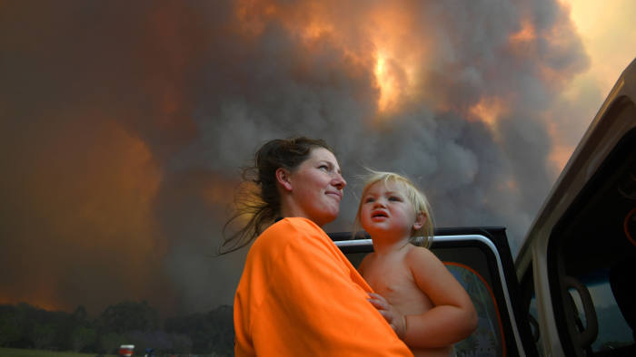 Mandatory Credit: Photo by DAN PELED/EPA-EFE/Shutterstock (10473518a) old daughter Charlotte look on as thick smoke rises from bushfires near Nana Glen, New South Wales, Australia, 12 November 2019 issued 13 November 2019). There are more than 50 fires burning around the state of New South Wales, with about half of those uncontained. Brushfires continue to burn in New South Wales, Nana Glen, Australia - 12 Nov 2019