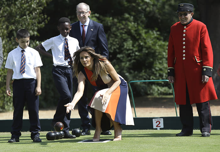 """U.S. First Lady Melania Trump plays bowls she meets British military veterans known as """"Chelsea Pensioners"""" at The Royal Hospital Chelsea in central London Friday, July 13, 2018. The pensioners, known for their scarlet coats and tricorne hats are a cherished British institution and are often seen parades, state events and other grand occasions. Smiling in rear is Philip May, the husband of British Prime Minister Theresa May. (AP Photo/Luca Bruno, Pool)"""