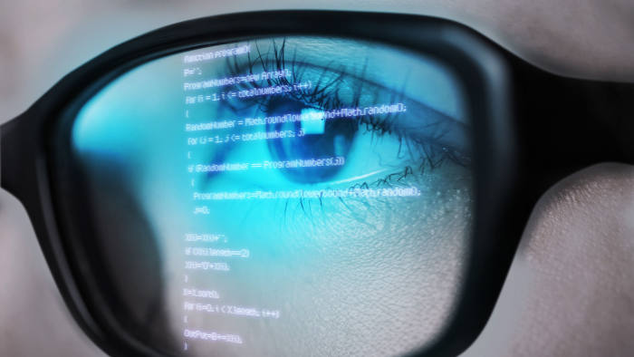 Programming code of computer monitor reflect to her eyeglasses.