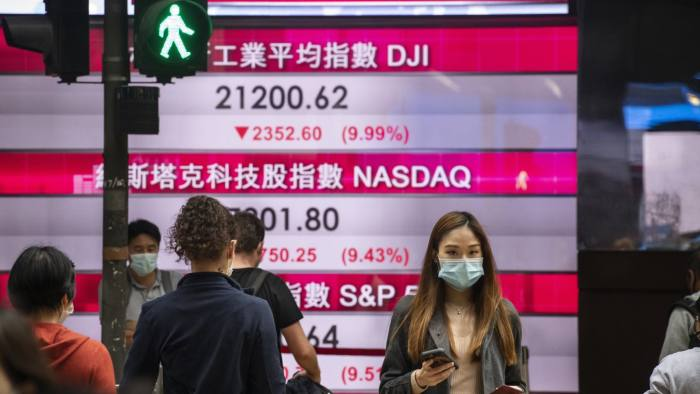 HONG KONG, CHINA - MARCH 13: Pedestrians wearing a face mask as a precautionary measure against the coronavirus, oficially named COVID-19, are seen walk past a stock market display board showing the Hang Seng Index results in Hong Kong on March 13, 2020. World markets have plunged by fears over the coronavirus outbreak. (Photo by Miguel Candela Poblacion/Anadolu Agency via Getty Images)