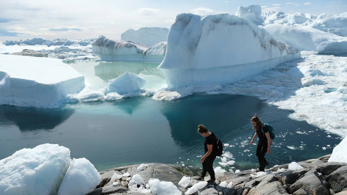 ILULISSAT, GREENLAND - JULY 30: Visitors walk among free-floating ice jammed into the Ilulissat Icefjord during unseasonably warm weather on July 30, 2019 near Ilulissat, Greenland. The Sahara heat wave that recently sent temperatures to record levels in parts of Europe is arriving in Greenland. Climate change is having a profound effect in Greenland, where over the last several decades summers have become longer and the rate that glaciers and the Greenland ice cap are retreating has accelerated. (Photo by Sean Gallup/Getty Images)