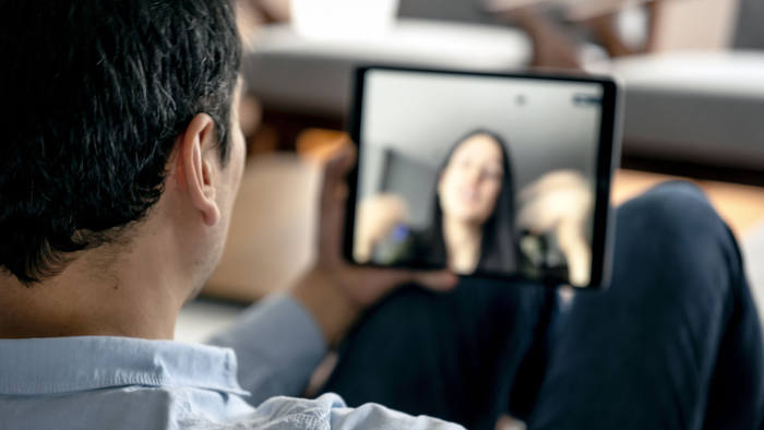 Man in a video conference with a woman. Using a tablet to make a video call.