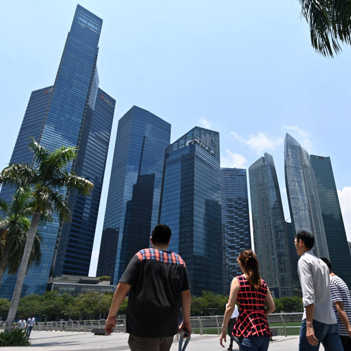 People walk along a promenade with a view of Marina Bay financial centre in Singapore on March 8, 2019. (Photo by Roslan RAHMAN / AFP) (Photo credit should read ROSLAN RAHMAN/AFP via Getty Images)
