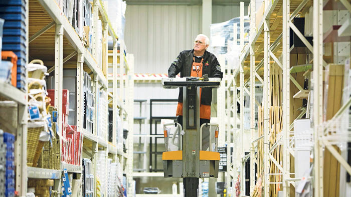 Pensioner Ken Slater, a B&Q employee, uses a lift to check stock levels at a store in Gillingham, U.K., on Tuesday, Nov. 30, 2010