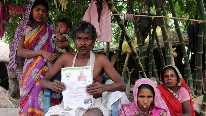 Nand Lal Mandhji, holds a letter about the Ayushman Bharat Medical Scheme, known as 'Modicare' as he sits outside his home with his family in Marwan village in the eastern state of Bihar, India, June 20, 2019. Picture taken June 20, 2019. REUTERS/Alasdair Pal - RC1252E27050