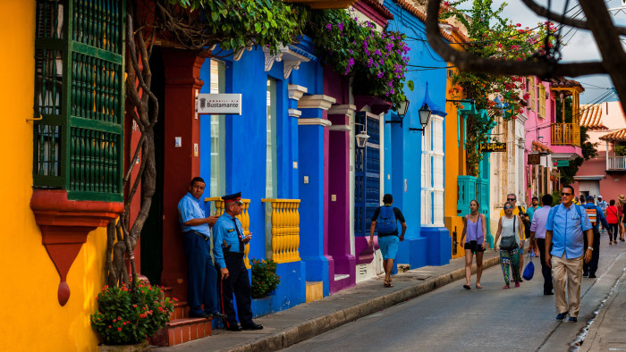 Tourists walk along the colorfully painted colonial houses in the street located within the historical walled city on December 12, 2017 in Cartagena, Colombia. After the peace agreement, ending a 52-year civil conflict and political stability in Colombia, Cartagena de Indias, a UNESCO World Heritage, experiences a tourism boom. The historic landmarks from the Spanish colonial times are being restored, private investments are visible in the city and an increased number of local people benefit from the boom of the travel related services. (Photo by Jan Sochor/Getty Images)