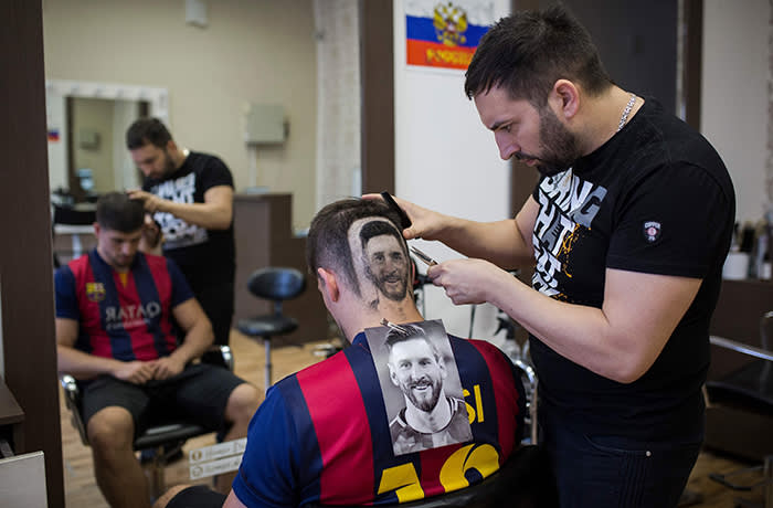 """TOPSHOT - Serbian hairdresser Mario Hvala creates a hair tattoo showing the portrait of Argentinian football player Lionel Messi on the head of a football fan in Novi Sad, Serbia, on June 10, 2018. A Serbian hairdresser proposes to his clients to draw with scissors on the back of their heads portraits of football superstars Lionel Messi and Cristiano Ronaldo for the forthcoming World Cup in Russia. Mario Hvala gives his creativity free rain ever since, 18 years ago, he made with scissors a tarantula on a client's head after suggesting him: """"Let's do something different."""" For the World Cup, which opens on June 14, 2018, he proposes to football afficionados to do the same thing with Messi and Ronaldo. / AFP PHOTO / VLADIMIR ZIVOJINOVICVLADIMIR ZIVOJINOVIC/AFP/Getty Images"""