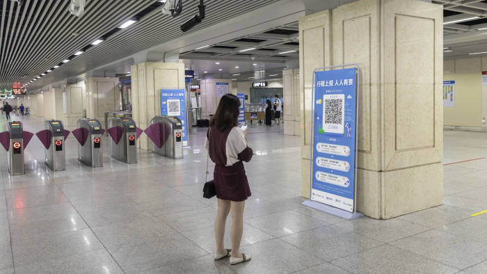 A passenger uses a smartphone at a banner displaying a quick response (QR) code enabling the inspection of one's travel history at a subway station in Wuhan, China, on Friday, May 1, 2020. The lifting on April 8 of the unprecedented lockdown on Wuhan -- where the virus pathogen first emerged -- was a milestone. Stringent nationwide restrictions in China meant the world's second-largest economy recorded its deepest contraction in decades over the first quarter. Photographer: Qilai Shen/Bloomberg