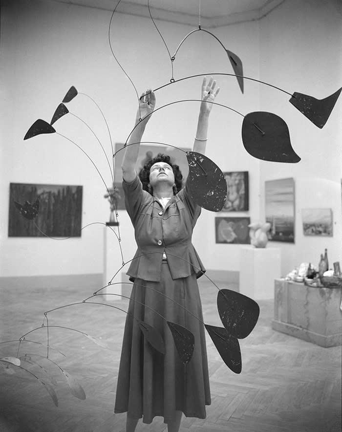 """Peggy Guggenheim with Alexander Calder """"Arc of Petals"""" at the Greek Pavilion, 24th Venice Biennale, 1948 © Fondazione Solomon R. Guggenheim, foto Archivio CameraphotoEpoche, donazione Cassa di Risparmio di Venezia, 2005."""