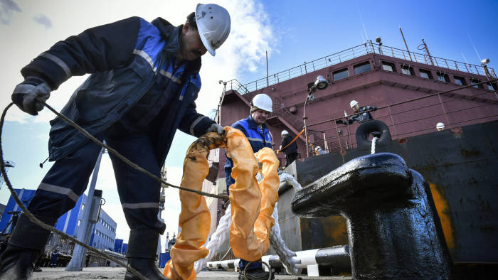 Workers fix mooring line of a floating power unit (FPU) Akademik Lomonosov being towed to Atomflot moorage of the Russian northern port city of Murmansk on May 19, 2018. - Akademik Lomonosov, the world's, so far, only nuclear floating power unit (FPU), has arrived to the port of Murmansk for being loaded with nuclear fuel before heading to eastern Siberia. Constructed by the state nuclear power firm Rosatom, the 144 by 30 metre (472 by 98 foot) ship holds two reactors with two 35 megawatt nuclear reactors that are similar to those used to power icebreaker ships. (Photo by Alexander NEMENOV / AFP)