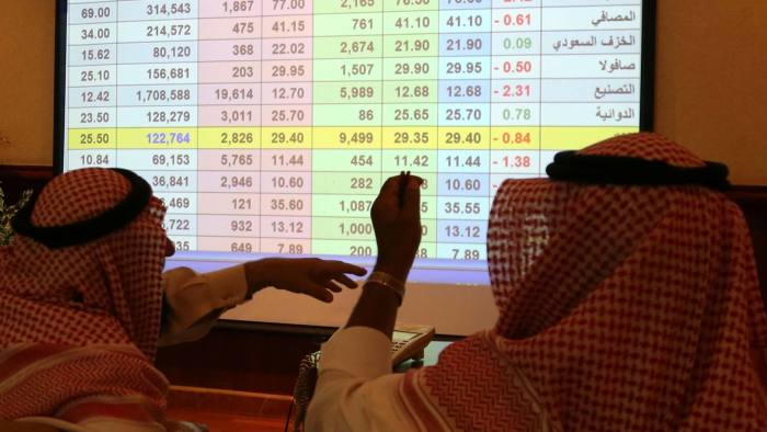 Saudi men look to a screen showing stock prices at ANB Bank, in Riyadh Saudi Arabia September 15, 2019. REUTERS/Stringer. NO RESALES. NO ARCHIVES