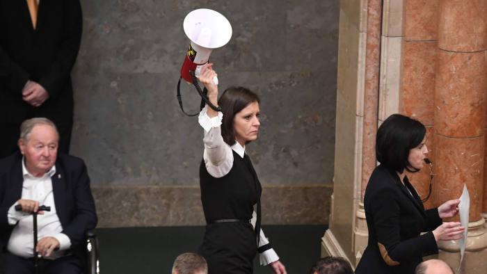 """Member of Parliament Bernadett Szel (C) holds a siren-horn next to Agnes Kohalmi (R) of the Hungarian Socialist Party in the hall of the parliament building in Budapest on December 12, 2018. - Rare scenes of chaos gripped the Hungarian parliament as it passed changes to the labour code proposed by Orban's party that critics have dubbed a """"slave law"""". The bill loosens labour rules by hiking the maximum annual overtime hours that employers can demand from 250 to 400 hours. (Photo by ATTILA KISBENEDEK / AFP)ATTILA KISBENEDEK/AFP/Getty Images"""