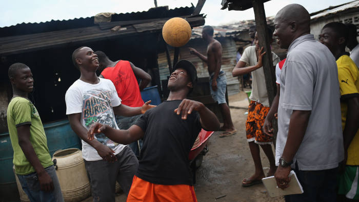 MONROVIA, LIBERIA - AUGUST 15: Young men show off their ball handling skills in the West Point slum on August 15, 2014 in Monrovia, Liberia. Poor sanitation and close quarters have contributed to the spead of the Ebola virus, which is transmitted through bodily fluids. The epidemic has killed more than 1,000 people in four West African countries. (Photo by John Moore/Getty Images)