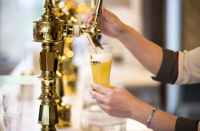 A bartender pours a glass of Kirin Ichiban beer at the Kirin Brewery Co. factory in Toride, Ibaraki, Japan, on Thursday, May 31, 2018. Kirin Holdings Co., the parent company of Kirin Co., aims to reach 100 billion yen ($910 million) in sales of food and beverages aimed at appealing to wellness concerns in the next two decades, according to chief executive officerYoshinori Isozaki. Photographer: Tomohiro Ohsumi/Bloomberg