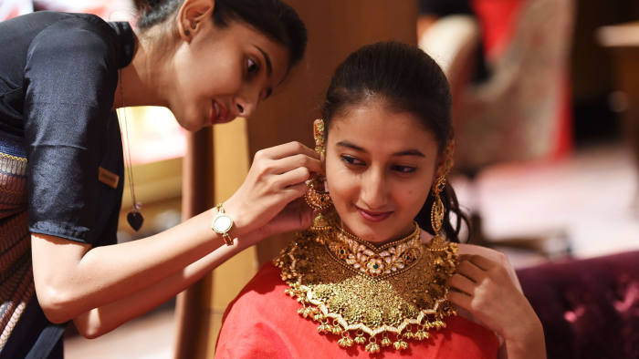 A customer tries a of 22 carat gold necklace at a jewelry shop in Ahmedabad on August 18, 2019. - Gold prices in India has shot surged closer to record highs recently. (Photo by SAM PANTHAKY / AFP)SAM PANTHAKY/AFP/Getty Images