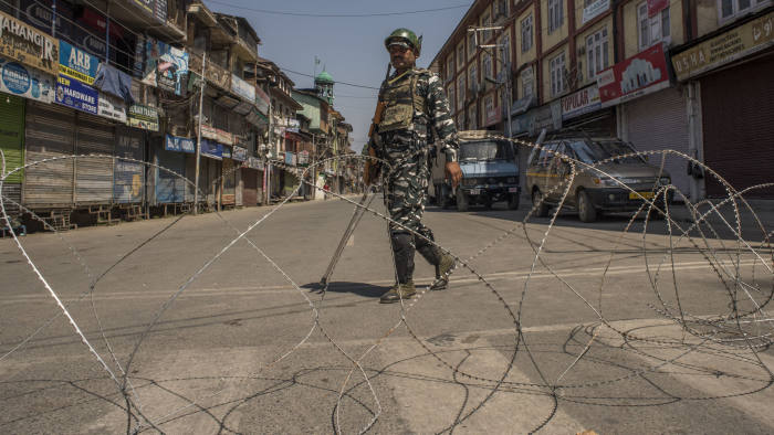 SRINAGAR, KASHMIR, INDIA - SEPTEMBER 09: Indian government forces guard the closed commercial hub in the city center during curfew like restrictions on September 09, 2019 in Srinagar, the summer capital of Indian administered Kashmir, India. Indian authorities have deployed thousands of government forces in Kashmir after India revoked articles 370 and 35A. The media are still facing a continued communications blackout as the blockade goes in to a second month. Article 35A of the Indian Constitution was an article that empowered the Jammu and Kashmir state's legislature to define permanent residents of the state and provided special rights and privileges to those permanent residents, also preventing non-locals from buying or owning property in the state. Prior to 1947, Jammu and Kashmir was a princely state under the British Empire. It was added to the Constitution through a Presidential Order. The Constitution Order 1954, (Application to Jammu and Kashmir) was issued by the President of India on 14 May, 1954 in accordance with Article 370 of the Indian Constitution, and with the concurrence of the Government of the State of Jammu and Kashmir. Kashmir has been a state under siege, with both India and Pakistan laying claim to it. Human rights organizations say more than 80,000 have died in the two decade long conflict with the Indian government claiming the number as 42,000. (Photo by Yawar Nazir/ Getty Images)