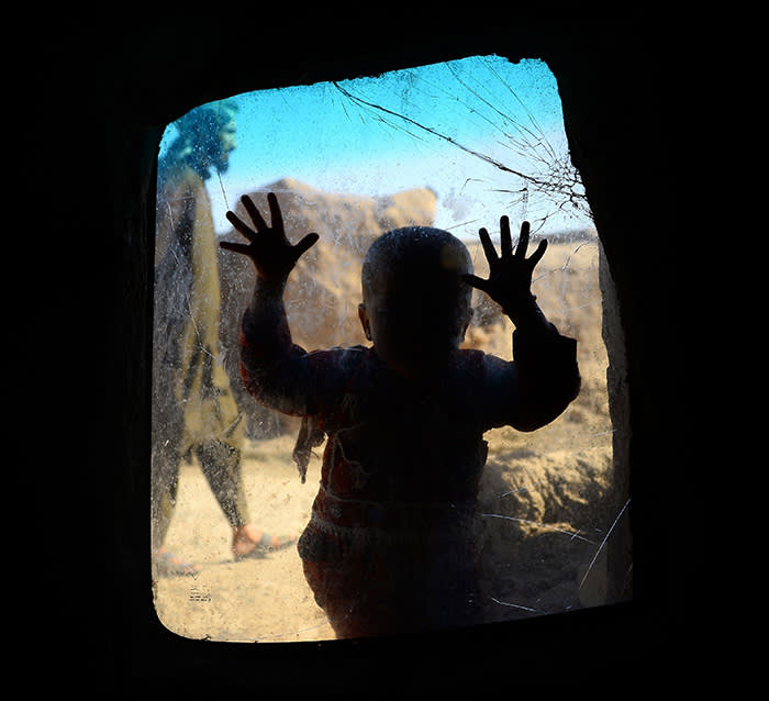 TOPSHOT - In this photograph taken on May 21, 2018 an internally displaced Afghan child looks on from a windows in her temporary home at a refugee camp on the outskirts of Herat. / AFP PHOTO / HOSHANG HASHIMIHOSHANG HASHIMI/AFP/Getty Images