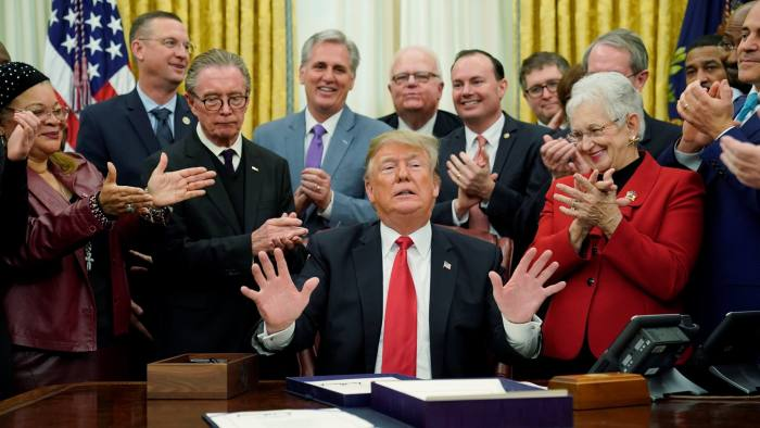 """U.S. President Donald Trump is applauded by Republican members of Congress and other attendees as he says he will not answer questions from reporters about an impending U.S. Government shutdown during a bill signing ceremony for the """"First Step Act"""" and the """"Juvenile Justice Reform Act"""" in the Oval Office of the White House in Washington, U.S., December 21, 2018. REUTERS/Joshua Roberts"""