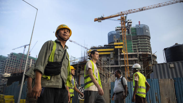 """COLOMBO, SRI LANKA - NOVEMBER 10: Chinese Construction workers head home after work on site at a new shopping mall called The Mall at One Galle Face which is part of the Chinese managed Shangri-La retails and office complex on November 10, 2018 in Colombo, Sri Lanka. In just a few years Port City will be the site of tall glass skyscrapers, a busy financial district, hospitals, hotels and even a theme park. As the political crisis escalates in Sri Lanka, former President Mahinda Rajapaksa""""u2019s return to power in late October has been watched with increasing concern by countries including the U.S., China and India. The re-entry of Rajapaksa could and raise the influence from Beijing and alter the power dynamics around the Indian Ocean. During Rajapaksa""""u2019s 2005-2015 presidency, Sri Lanka saw an influx of Chinese investment and economic support since he relied heavily on China for economic support, military equipment and political cover. While ousted Prime Minister Ranil Wickremesinghe sought to balance relations with New Delhi and Beijing, Rajapaksa made clear his willingness to accept Chinese money even in the face of unreasonable terms while reports from the Central Bank estimated the debt owed to China could be as much as $5 billion and growing every year. Chinese investments paid for a new port, a new airport and new railway on Sri Lanka""""u2019s southern coast, among other projects in Colombo, which forced the government to sell strategic assets to Beijing, such as the Hambantota port, when it wasn't able to meet liabilities. For China, the relation with Sri Lanka ties back thousands of years when it was a stop along the old Silk Road trade routes, as it is now known to be a critical link for its Belt and Road Initiative, which aims to expand trade across 65 countries from the South Pacific through Asia to Africa and Europe. (Photo by Paula Bronstein/Getty Images)"""