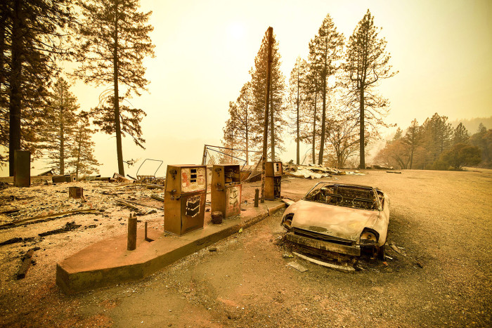 """TOPSHOT - A burnt car and a gas station remain visible after the """"Camp"""" fire tore through the region near Pulga, east of Paradise, California on November 11, 2018. - Search teams scoured the carnage of California's most destructive ever wildfire for victims on Sunday, as the state-wide death toll rose to 26 with high winds hampering the effort to rescue property and save lives. At least 23 people have lost their lives in and around the Paradise community of 27,000, according to an official count by authorities. (Photo by Josh Edelson / AFP) (Photo credit should read JOSH EDELSON/AFP/Getty Images)"""