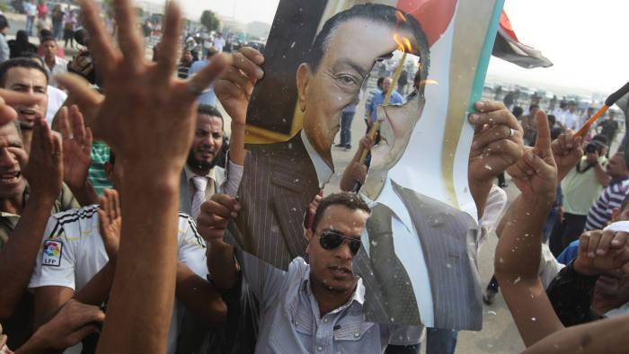 Anti-(Hosni) Mubarak protestors burn a portrait of the former Egyptian president outside the courtroom where his trial resumed off-camera on September 5, 2011. AFP PHOTO/KHALED DESOUKI (Photo credit should read KHALED DESOUKI/AFP via Getty Images)