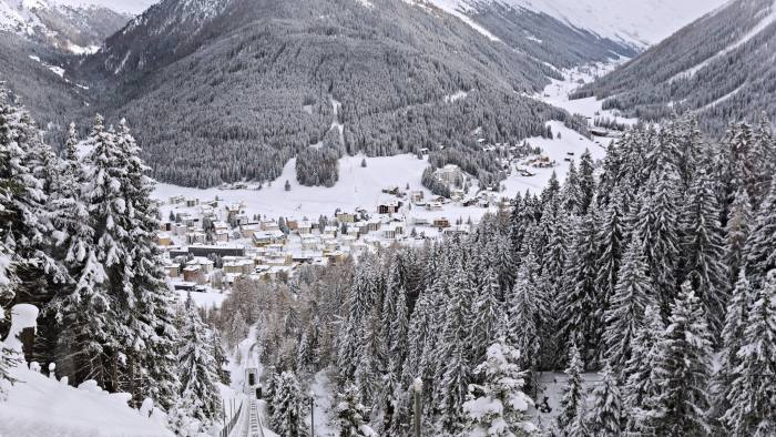 Snow covered trees and mountains surround buildings in Davos, Switzerland, on Sunday, Jan. 15, 2017. World leaders, influential executives, bankers and policy makers attend the 47th annual meeting of the World Economic Forum (WEF) in Davos from Jan. 17-20. Photographer: Michele Limina/Bloomberg