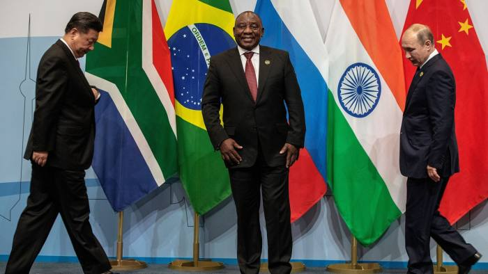 TOPSHOT - (LtoR) China's President Xi Jinping, South Africa's President Cyril Ramaphosa and Russia's President Vladimir Putin arrive to pose for a group picture during the 10th BRICS (acronym for the grouping of the world's leading emerging economies, namely Brazil, Russia, India, China and South Africa) summit on July 26, 2018 at the Sandton Convention Centre in Johannesburg, South Africa. (Photo by Gianluigi GUERCIA / POOL / AFP) (Photo credit should read GIANLUIGI GUERCIA/AFP/Getty Images)
