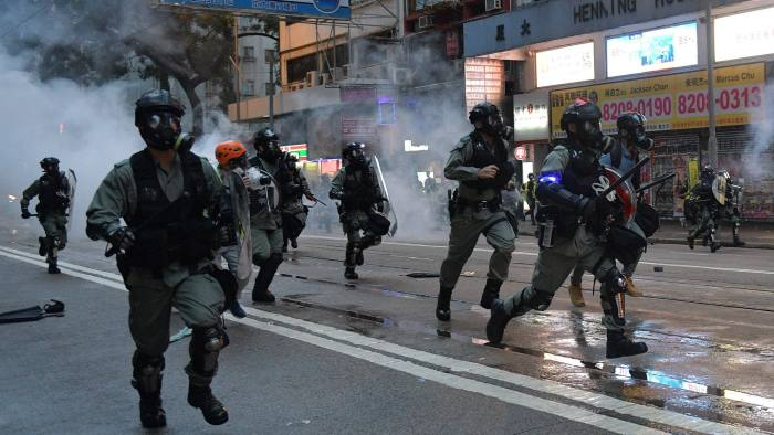 Hong Kong police advance on protesters during clashes the Wanchai district in Hong Kong on October 6, 2019. - A Hong Kong judge on October 6 rejected a challenge to an emergency law criminalising protesters wearing face masks as democracy activists hit the streets again in defiance of the ban despite half the city's subway stations remaining closed. (Photo by Nicolas ASFOURI / AFP) (Photo by NICOLAS ASFOURI/AFP via Getty Images)