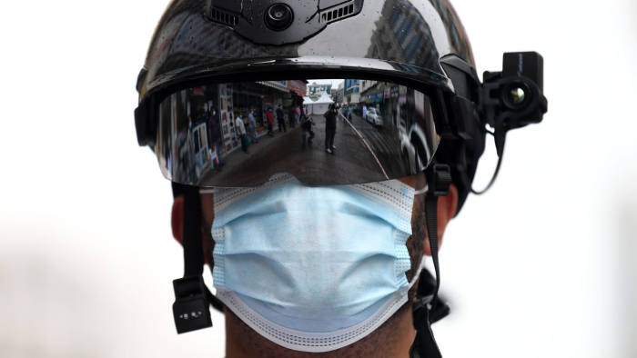Foreign workers standing in line as they wait to be checked for the novel coronavirus at a testing centre in the Naif area of the Gulf Emirate of Dubai, are reflected against the helmet of a policeman, on April 15, 2020. (Photo by KARIM SAHIB / AFP) (Photo by KARIM SAHIB/AFP via Getty Images)