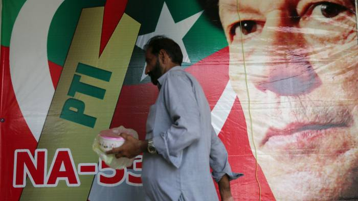 A man walks past an image of cricket star-turned-politician Imran Khan, chairman of Pakistan Tehreek-e-Insaf (PTI) at a market in Islamabad, Pakistan, July 27, 2018. REUTERS/Athit Perawongmetha