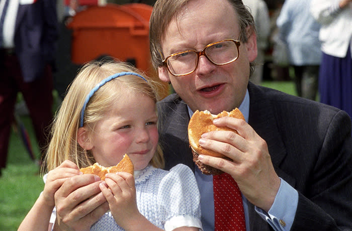 Agriculture minister John Gummer with his 4 year old daughter Cordelia, tuck into a beefburger on a visit to the East Coast Boat Show in Ipswich. The possilbe danger of the BSE disease in British beef was scuppered by the minister. * in an attempt to calm public fears when the beef scare first broke in 1990. Mr Gummer, now Environment Secretary snapped angrily at James Naughtie, presenter of Radio 4's Today programme, when he asked if Mr Gummer now regretted posing for the picture. *25/10/2000 Mr Gummer and other senior members of the Thatcher and Major administrations are bracing themselves for harsh criticism of their handling of the BSE crisis, as the Government publishes the long-awaited results of the inquiry into Britain's biggest public health disaster. Lord Phillips' report, to be published Thursday October 26 2000 is expected to condemn the former Tory government's slow reaction to the crisis and ministers' refusal to accept that humans might be made ill by eating beef from infected cows. 26/10/00: Mr Gummer and other senior members of the Thatcher and Major administrations are bracing themselves for harsh criticism of their handling of the BSE crisis, as the Government publishes the long-awaited results of the inquiry into Britain's biggest public health disaster. Lord Phillips' report, published Thursday October 26 2000, is expected to condemn the former Tory government's slow reaction to the crisis and ministers' refusal to accept that humans might be made ill by eating beef from infected cows.