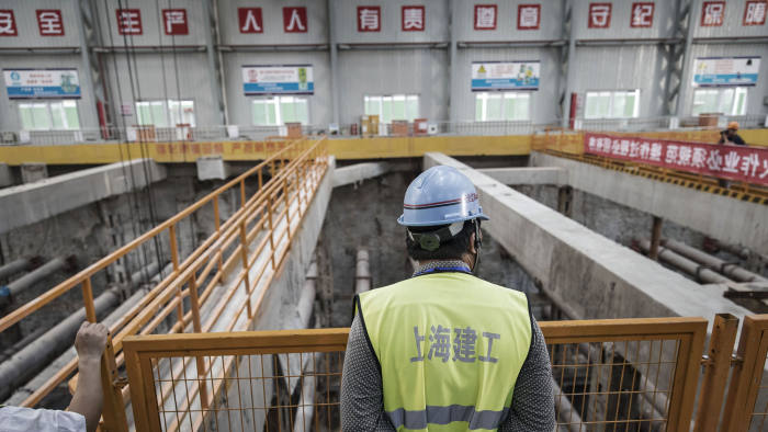 A worker stands overlooking an open pit at a construction site for Line 14 of the Shanghai Metro system in Shanghai, China, on Tuesday, July 11, 2017. The world's second-largest economy is forecast to slow from the first quarter, when it posted the first back-to-back quarterly acceleration in seven years, though it is still on track to remain above the leadership'sgrowthtarget of at least 6.5 percent. Photographer: Qilai Shen/Bloomberg