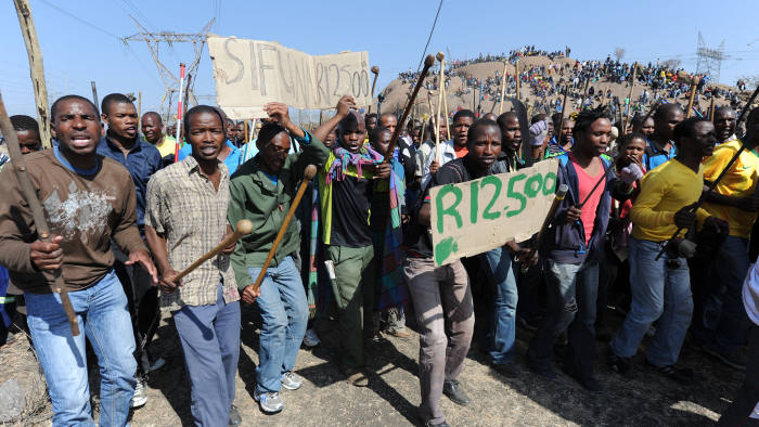 Miners demonstrate at a mountain close to the mine near Rustenburg where they are demanding that their wages are more than tripled on August 16, 2012. Clashes broke out over the weekend between members of the upstart Association of Mineworkers and Construction Union (AMCU) and the powerful National Union of Mineworkers (NUM). AFP PHOTO (Photo credit should read -/AFP/GettyImages)