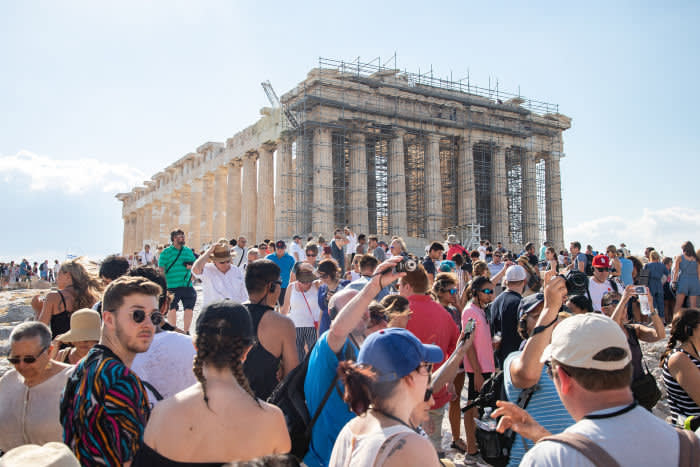 Overcrowded with thousands of tourists and visitors during the morning in Parthenon, Acropolis in Athens, Greece, the Greek capital. The ancient hill of Acropolis, including the worldwide known Parthenon and remains of many ancient buildings of great architectural and historic significance as the Erechtheion, Propylaia, Temple of Athena Nike and more. Acropolis severed heavy damage during the Ottoman occupation. It is nowadays UNESCO World Heritage site since 1987. The Parthenon was a temple dedicated to the ancient Greek goddess Athena, it was built in 432BC by the architects Iktinos and Calicrates. There were also famous sculptures from Phidias inside. The Acropolis on July 15. 2019 (Photo by Nicolas Economou/NurPhoto via Getty Images)